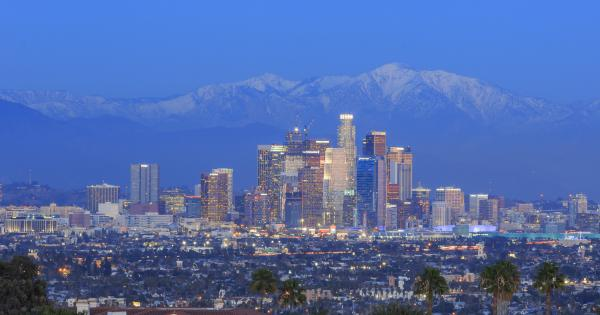 A view of the Los Angeles skyline with snow-topped mountains in the background