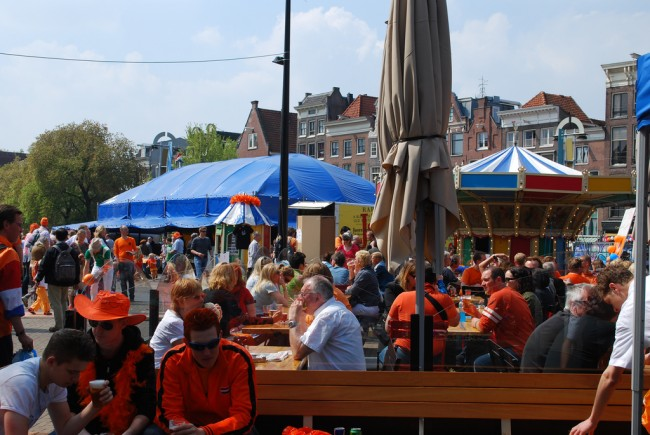 People dressed in orange eating and drinking at a funfair