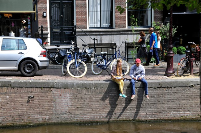 Two people sit on the edge of the canal