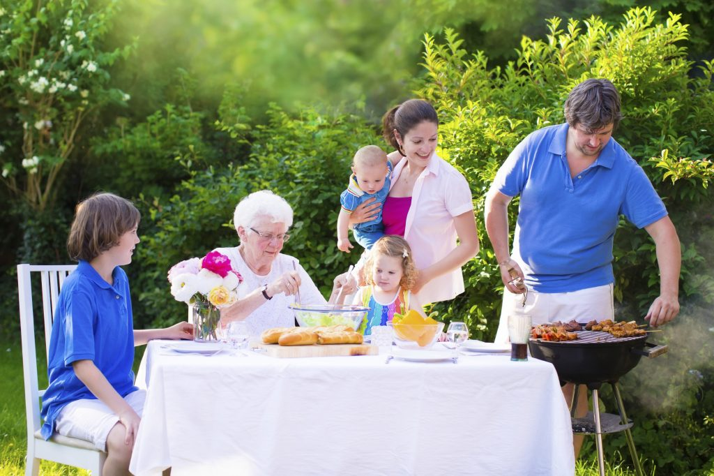 Grill barbecue backyard party. Happy big family - young mother and father with kids, teen age son, cute toddler daughter and a little baby, enjoying BBQ lunch with grandmother eating grilled meat in the garden with salad and bread.