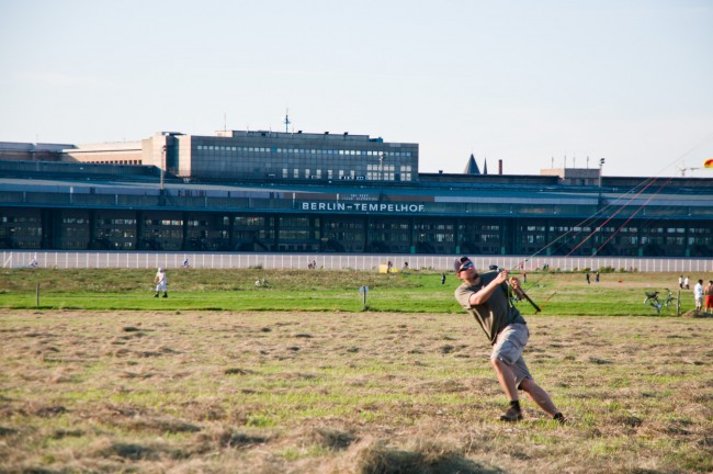 A man flying a kite in Tempelhof Park Berlin